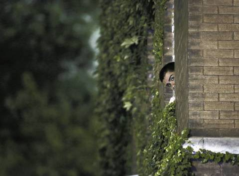 Neighbor Alejandro Cabada watches the scene where 13 people, including a 3-year-old, were shot at Cornell Square Park in the Back of the Yards neighborhood of Chicago.