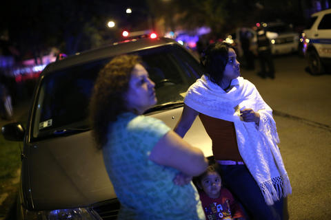 Mayra Rodriguez, (right) with her mother Elvia Gonzalez (left) and daughter Delila Cruz, 2, watch the scene where at least 13 people, including a 3-year-old, were shot at Cornell Square Park in the Back of the Yards neighborhood of Chicago.