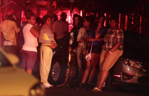 People gather at the scene of a multiple shooting near the intersection of 50th and Wood Streets in Chicago. At least 13 people were shot, including a 3-year-old, in the incident.
