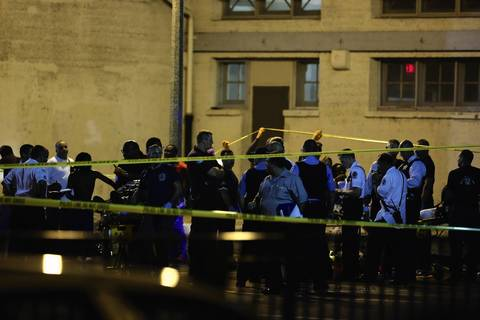 Chicago police gather at the scene of a multiple shooting near the intersection of 50th and Wood Streets in Chicago. At least 13 people were shot, including a 3-year-old, in the incident.