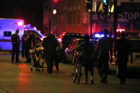 Emergency personnel transport victims from the scene where 13 people, including a 3-year-old, were shot at Cornell Square Park in the Back of the Yards neighborhood of Chicago.