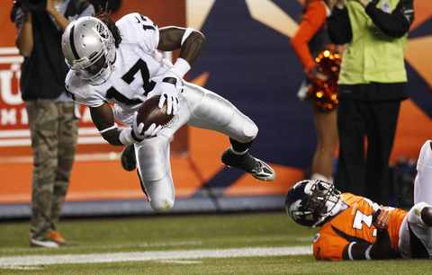 Oakland Raiders wide receiver Denarius Moore (L) flies over the goal line for a 73-yard touchdown past Denver Broncos cornerback Kayvon Webster in the second quarter of their NFL football game in Denver September 23, 2013.
