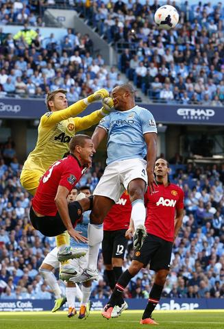 Manchester City's Vincent Kompany (R) gets hit in his face as he is challenged by Manchester United's David de Gea (L) and Nemanja Vidic during their English Premier League soccer match at the Etihad Stadium in Manchester, northern England, September 22, 2013.