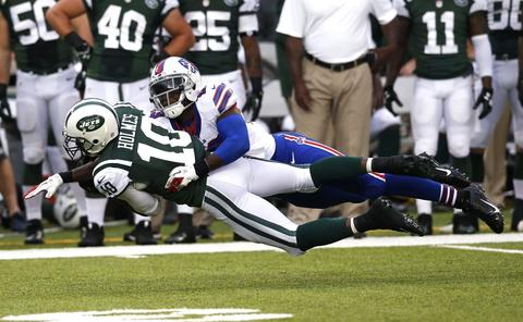 New York Jets' Santonio Holmes (10) makes a diving catch in front of Buffalo Bills' free safety Aaron Williams (23) during the second quarter in their NFL football game in East Rutherford, New Jersey, September 22, 2013.