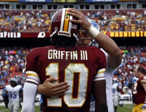 Washington Redskins quarterback Robert Griffin III is consoled by Detroit Lions quarterback Matthew Stafford after their NFL football game in Landover September 22, 2013.