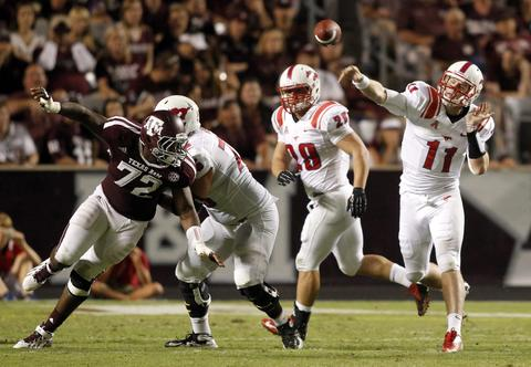 SMU quarterback Garrett Gilbert passes as offensive lineman Kris Weeks (2nd L)  blocks Texas A&M defensive lineman Gavin Stansbury (L) in the second half of their NCAA football game at Kyle Field in College Station, Texas September 21, 2013.