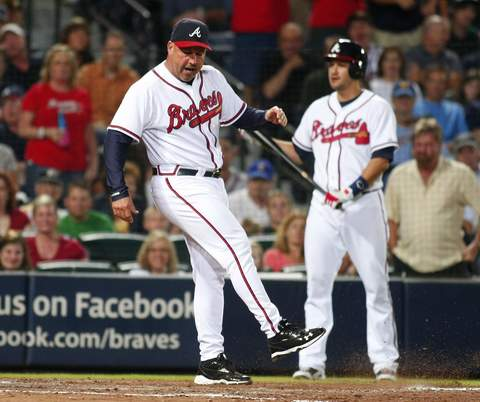 Atlanta Braves manager Fredi Gonzalez kicks dirt on the plate after arguing with home plate umpire Angel Hernandez (not seen) during the bat of Paul Janish (R) in the seventh inning at their MLB National League baseball game in Atlanta, Georgia  September 23, 2013.