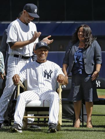 New York Yankees relief pitcher Mariano Rivera smiles as he sits in a rocking chair made of baseball bats after it was presented to him by his teammates as he is honored during a pregame ceremony before the MLB Interleague game with the San Francisco Giants at Yankee Stadium in New York, September 22, 2013. Looking on is New York Yankees captain Derek Jeter and Rivera's wife Clara (R).