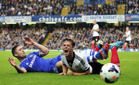 Fulham's English midfielder Scott Parker (R) reacts as Chelsea's English defender Gary Cahill (L) lands on top of him as they vie for the ball during the English Premier League football match between Chelsea and Fulham at Stamford Bridge in London on September 21, 2013. TOPSHOTS/AFP PHOTO/GLYN KIRK RESTRICTED TO EDITORIAL USE. No use with unauthorized audio, video, data, fixture lists, club/league logos or live services. Online in-match use limited to 45 images, no video emulation. No use in betting, games or single club/league/player publications.GLYN KIRK/AFP/Getty Images ORG XMIT: 170561782