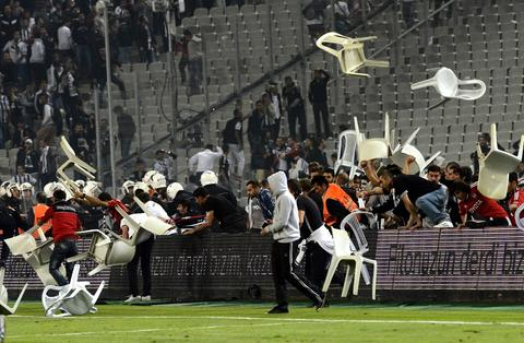 Besiktas football team supporters fight with Anti riot police officers during the Turkish super league football match Besiktas vs Galatasaray on September 22, 2013, at the Ataturk stadium in Istanbul.