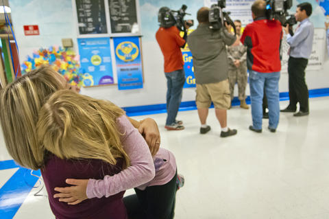 2013.09.23 - Southington, CT - Madison Howes, a Flanders Elementary third-grader, hugs her mother, Izabela Howes, while her father, Staff Sergeant Michael Howes, is interviewed by local media.
