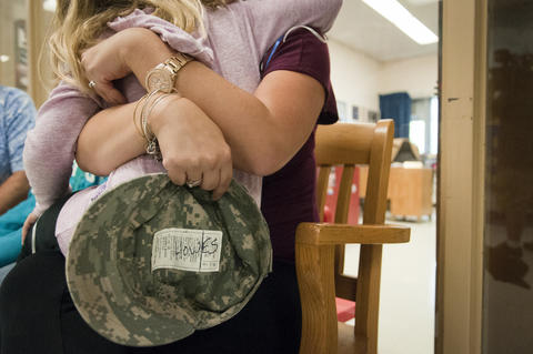 2013.09.23 - Southington, CT - Madison Howes, a Flanders Elementary third-grader, hugs her mother, Izabela Howes, while her father, SSG Michale Howes, is interviewed by local media.