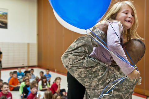2013.09.23 - Southington, CT - Madison Howes, a Flanders Elementary third-grader, is lifted by her father, Staff Sergeant Michael Howes, as she sees him for the first time since his nine-month military deployment to Djibouti.