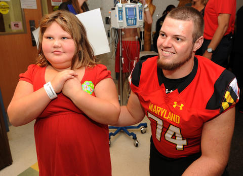 Terps offensive lineman Nick Klemm takes a picture with patient Trinity Merritt, 7.