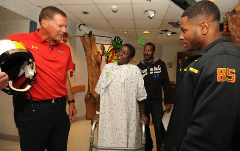 Randy Edsall, left, and Tehuti Miles, far right, chat with patient, Kahron Thompson,13. Second from right is Tehuti 's stepfather, Samuel Hunter.