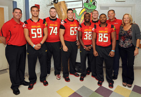 Maryland coach Randy Edsall and his wife, Eileen (both far right), pose for pictures with members of the Terps football team.