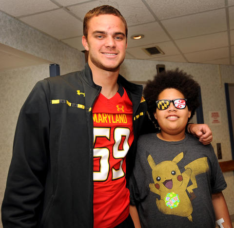 Terps football player Greg Parcher poses with Jaylen Worthy, 12, who's sporting the Maryland colors in glasses he received from the team.