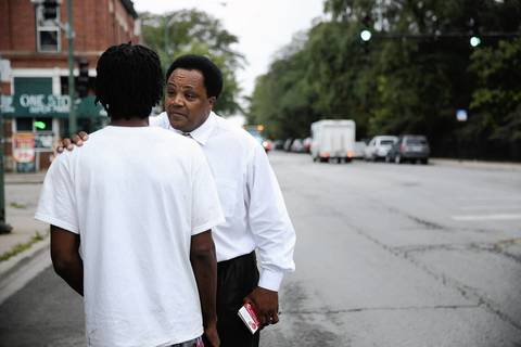 Community activist Andrew Holmes talks with one of the 13 victims shot Thursday night at Cornell Square Park in the Back of the Yards neighborhood of Chicago.