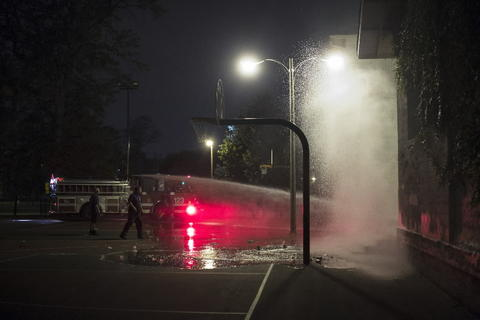 Chicago firefighters wash the scene where at least 13 people, including a 3-year-old, were shot at Cornell Square Park in the Back of the Yards neighborhood in Chicago.