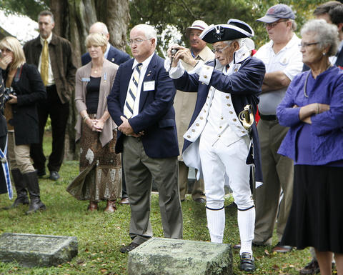Mike Lyman, dressed in colonial costume, takes a photo during the ceremony that will place a wreath at the grave of Thomas Nelson, Jr. at Grace Episcopal Church.  To his left is Thomas Page Nelson. Jr., whose 4th great grandfather is the one being honored.