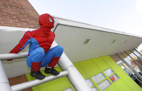 If your need to be a newspaper photographer goes beyond making photos, then the Party Station on Jefferson Avenue has a Spiderman costume for you. Here, Shawn Hammer leaps from a car to a ladder to check out the Halloween possibilities of the costume.  Photo taken October 5, 2012.