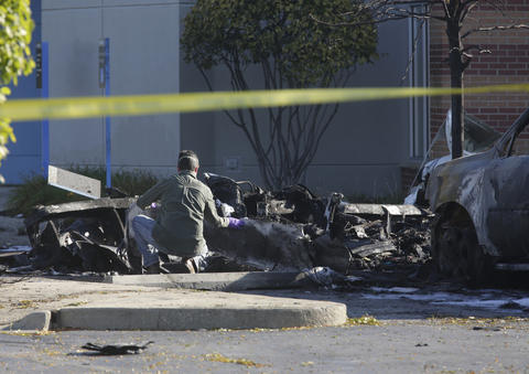 An investigator inspects the charred remains of a small single-engine plane in the Chase Bank branch parking lot at 262 S. Weber Rd. in Bolingbrook on Thursday. The plane crashed Wednesday afternoon, taking the lives of a husband and wife.