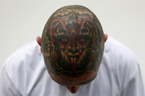 Jakub displays a tattoo on his head during the ninth London International Tattoo Convention in London September 27, 2013.