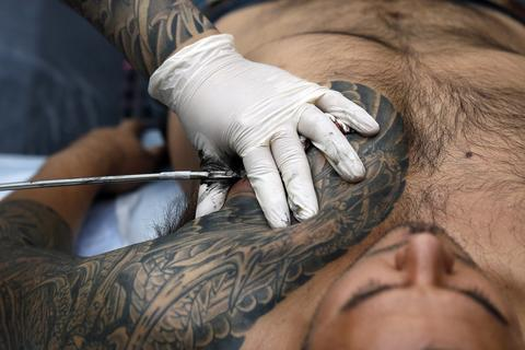 A man is tattooed by tattoo artist Chosu Horikazu (L) during the ninth London International Tattoo Convention in London September 27, 2013.