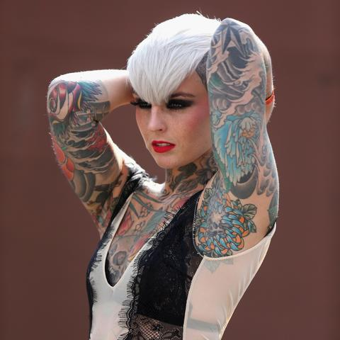 A tattooed model poses for photographers at the London Tattoo Convention in Tobacco Dock on September 27, 2013 in London, England. Over 300 tattoo artists from around the world are to showcase their body art in 26 halls at the convention which also features live music and tattoo competitions.