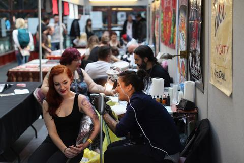 Body art enthusiasts receive tattoos at the London Tattoo Convention in Tobacco Dock on September 27, 2013 in London, England. Over 300 tattoo artists from around the world are to showcase their body art in 26 halls at the convention which also features live music and tattoo competitions.