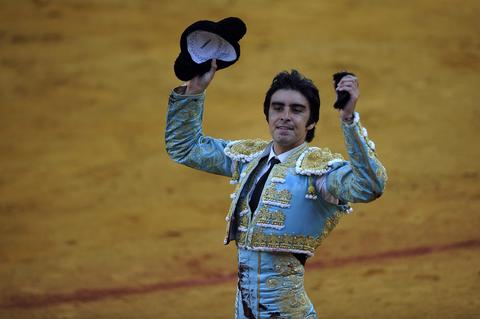 Spanish matador Miguel Angel Perea celebrates with a ear after killing a bull during a bullfight at the Maestranza bullring in Sevilla on September 28, 2013.