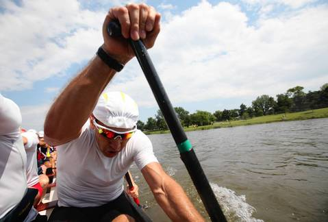 Wojtek Wasilewski, co-captain of Windy City Dragons¿digs water during practice at a mini-camp with members of Dubuque Dragon Boat Association from Iowa on Lake Arlington in Arlington Heights.