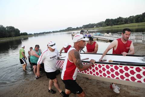 Members of Windy City Dragons pull the dragon boat on land after the team practice.