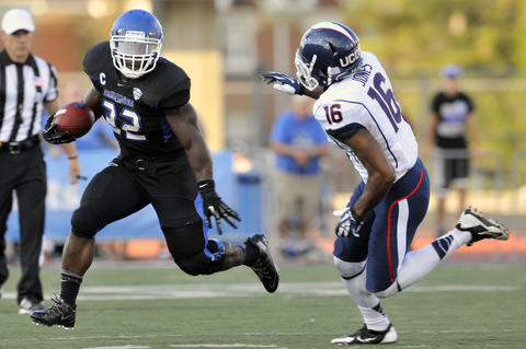 Branden Oliver of Buffalo rushes past Byron Jones during UConn's 41-12 loss.