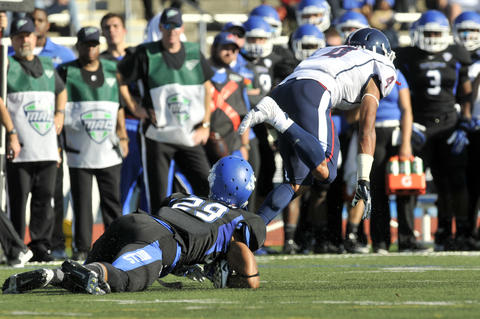 Deshon Foxx of UConn loses a shoe as Adam Redden of Buffalo loses his helmet attempting to tackle Foxx in the first half Buffalo's 41-12 win.