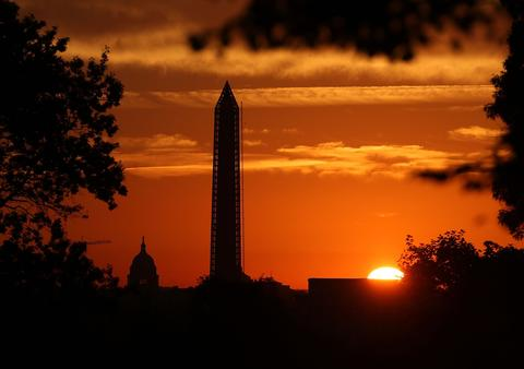 The sun begins to rise behind the U.S. Capitol and The Washington Monument, September 30, 2013 in Washington, DC.