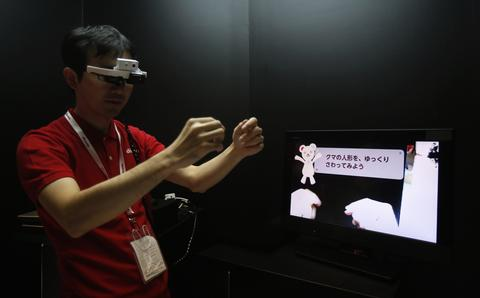 "A staff member of NTT DoCoMo Inc wears a head-mounted ""intelligent glass"", which enables the display of touchable augmented reality, during a photo opportunity at a media preview of CEATEC (Combined Exhibition of Advanced Technologies) JAPAN 2013 in Chiba, east of Tokyo, September 30, 2013. A total of 587 companies and organizations are exhibiting at CEATEC JAPAN 2013, which will be held until October 5, 2013."
