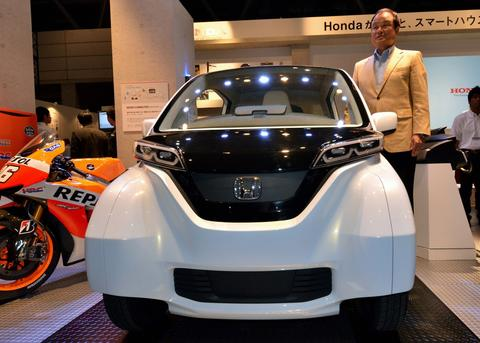 Japan's auto maker Honda Motor president Takanobu Ito displays the prototype model of a three-seater micro commuter at the Ceatec electronics trade show in Chiba, Tokyo on October 1, 2013. Asia's largest electronics trade show Ceatec will run from October 1-5 and exhibit some of the latest electronics technology products.
