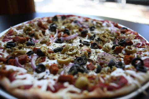The supreme pizza with homemade sausage, pepperoni, olives, onion and vegan cheese at Kitchen 17, 613 W. Briar Pl.