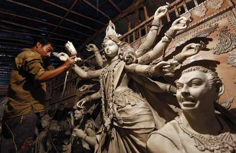 An artist sprays paint on an idol of the Hindu goddess Durga at a workshop ahead of the Durga Puja festival in New Delhi October 1, 2013. The Durga Puja festival will be celebrated from October 11 to October 14, and is the biggest religious event for Bengali Hindus. Hindus believe that the goddess Durga symbolises power and the triumph of good over evil.