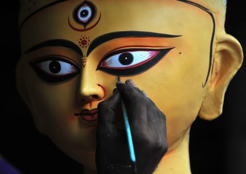 An Indian artisan paints a clay idol of Hindu goddess Durga inside his workshop in Kumartoli, the idol makers' village of Siliguri, on October 2, 2013. The economic slowdown and rising inflation add to the difficulties of the artisans ahead of this five-day Durga Puja festival to be celebrated in October. The event commemorates the slaying of a demon king Mahishasur by goddess Durga, marking the triumph of good over evil.