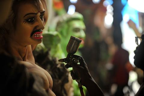 An Indian artisan sprays colour on a clay idol of Hindu goddess Durga inside his workshop in Kumartoli, the idol makers' village of Siliguri, on October 2, 2013. The economic slowdown and rising inflation add to the difficulties of the artisans ahead of this five-day Durga Puja festival to be celebrated in October. The event commemorates the slaying of a demon king Mahishasur by goddess Durga, marking the triumph of good over evil.