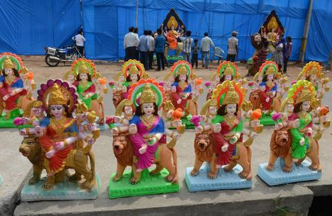 Indian devotees bargain to buy an idol of the Hindu goddess Durga ahead of the Dushhera-Vijaya Dashami festival at outside of a workshop in Hyderabad on October 2, 2013.  Durga Puja, the annual Hindu festival that involves worship of the goddess Durga who symbolizes power and the triumph of good over evil in Hindu mythology, culminates in the immersion of idols in bodies of water.