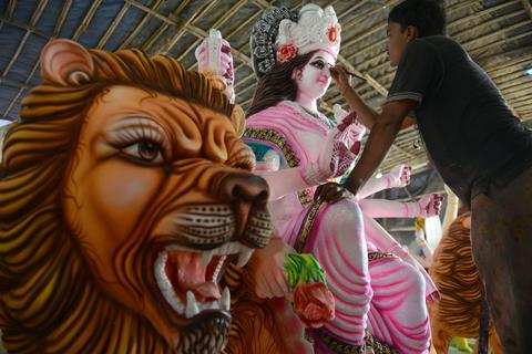 An Indian artisan gives the final touches to an idol of the Hindu goddess Durga ahead of the Dushhera-Vijaya Dashami festival at a workshop in Hyderabad on October 2, 2013.  Durga Puja, the annual Hindu festival that involves worship of the goddess Durga who symbolizes power and the triumph of good over evil in Hindu mythology, culminates in the immersion of idols in bodies of water.