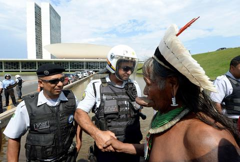 The chief of the Kayapo indigenous people, Raoni (R) greets policemen during a demo in front of the National Congress in Brasilia on October 2, 2013. Indigenous people from several ethnic groups will concentrate in the Brazilian capital to demand more support from the federal government during the National Indigenous Mobilization Week.