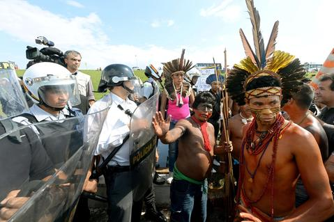 Brazilian natives stand in front of riot policemen guarding the National Congress in Brasilia on October 2, 2013. Indigenous people from several ethnic groups will concentrate in the Brazilian capital to demand more support from the federal government during the National Indigenous Mobilization Week.