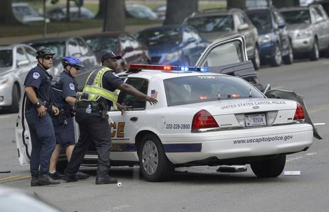 "Police officers attend to an officer in a cruiser that was wrecked after shots fired were reported near 2nd Street NW and Constitution Avenue on Capitol Hill in Washington, DC, on October 3, 2013. The US Capitol was placed on security lockdown Thursday after shots were fired outside the complex, senators said. ""Shots fired outside the Capitol. We are in temporary lock down,"" Senator Claire McCaskill said on Twitter. Police were seen running within the Capitol building and outside as vehicles swarmed to the scene."