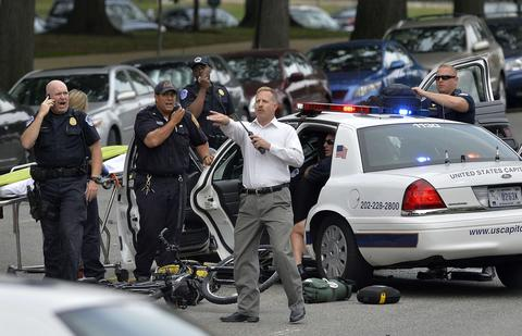 """Police officers attend to an officer in a cruiser that was wrecked after shots fired were reported near 2nd Street NW and Constitution Avenue on Capitol Hill in Washington, DC, on October 3, 2013. The US Capitol was placed on security lockdown Thursday after shots were fired outside the complex, senators said. """"Shots fired outside the Capitol. We are in temporary lock down,"""" Senator Claire McCaskill said on Twitter. Police were seen running within the Capitol building and outside as vehicles swarmed to the scene."""