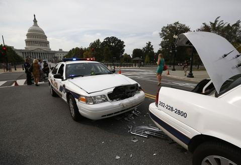 Two U.S. Capitol Police cars sit damaged after colliding during a shooting in Washington, October 3, 2013. The Capitol was locked down briefly on Thursday after gunshots were fired outside the building following a car chase across central Washington and a number of people including a law enforcement officer were hurt, officials said.