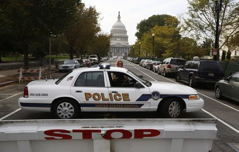 A U.S. Capitol Police officer blocks access to the U.S. Capitol building following a shooting in Washington, October 3, 2013. The Capitol was locked down briefly on Thursday after gunshots were fired outside the building following a car chase across central Washington and a number of people including a law enforcement officer were hurt, officials said.